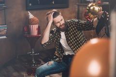 Hombre joven barbudo con el dolor de cabeza que sostiene el sujetador negro Foto de archivo libre de regalías