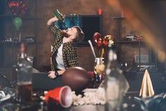 Hombre joven barbudo con el vino de consumición de la resaca de la botella Imagen de archivo libre de regalías