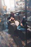 Hombre joven barbudo con la botella que duerme en el sofá después de partido Fotografía de archivo