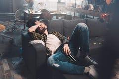 Hombre joven barbudo con la botella que miente en el sofá después de partido Foto de archivo