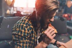 Hombre joven barbudo con resaca que come la pizza después de partido Foto de archivo