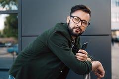 Hombre joven barbudo en las lentes que sostienen smartphone Imágenes de archivo libres de regalías