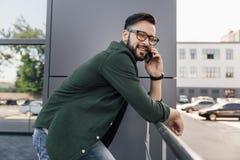Hombre joven barbudo en lentes usando smartphone Fotografía de archivo