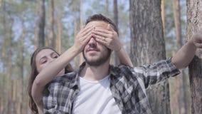 Hombre joven barbudo hermoso en el bosque del pino, la muchacha del retrato que cubre sus ojos con las manos de detrás el primer almacen de metraje de vídeo