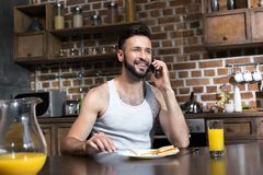 hombre joven barbudo hermoso que usa smartphone mientras que desayunando imagenes de archivo