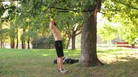 Hombre joven barbudo que hace tirón-UPS en lazos de la aptitud en un parque de la sol cantidad lenta de 4K MES metrajes