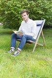 Hombre joven barbudo que se sienta en el jardín que mira la cámara Fotografía de archivo