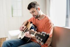Hombre joven barbudo que se sienta en el sofá y que toca la guitarra Imágenes de archivo libres de regalías