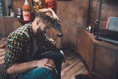 Hombre joven barbudo que sufre de dolor de cabeza después de partido Fotografía de archivo