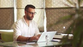Hombre joven barbudo que trabaja en la oficina, ordenador portátil, cuidadosamente mirando a través de los vidrios, sonriendo Fre metrajes