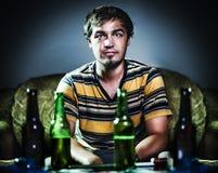 Hombre joven borracho en el sofá Fotos de archivo libres de regalías
