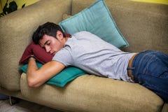 Hombre joven borracho que duerme en el sofá de la sala de estar Foto de archivo