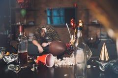 Hombre joven borracho que duerme en el sofá en sitio sucio imagenes de archivo