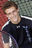 Hombre joven cabelludo de Brown que sonríe con la raqueta de tenis Imagen de archivo