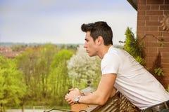Hombre joven cabelludo oscuro hermoso que mira hacia fuera encendido Fotos de archivo