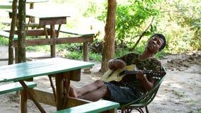 Hombre joven camboyano feliz que juega en la guitarra clásica
