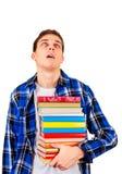 Hombre joven cansado con libros Imagen de archivo