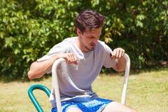 Hombre joven cansado después del ejercicio al aire libre en el aparato de remar fotografía de archivo