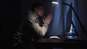 Hombre joven cansado que trabaja en el ordenador en la noche, frente del rasguño almacen de metraje de vídeo