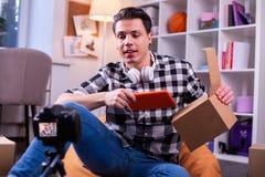 Hombre joven carismático comunicativo en la camisa a cuadros que sostiene la nueva tableta imagenes de archivo