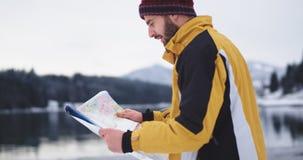 Hombre joven carismático del primer con la mirada tenida roja alrededor de sostener un mapa para conseguir el destino siguiente,  almacen de video