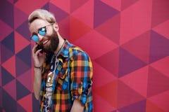 Hombre joven carismático hermoso que habla en el teléfono móvil, en un backgound del multicolore imagen de archivo
