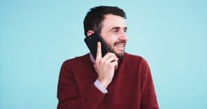 Hombre joven carismático sonriente que habla en su teléfono delante de la cámara en el estudio con una pared azul del fondo almacen de metraje de vídeo