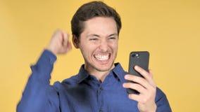 Hombre joven casual que celebra éxito mientras que usando Smartphone en fondo amarillo metrajes