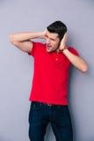 Hombre joven casual que cubre sus oídos Imagenes de archivo