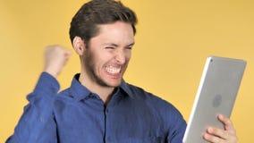 Hombre joven casual que gana en la tableta, fondo amarillo metrajes