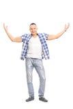 Hombre joven casual, sonriendo y gesticulando con sus manos Imágenes de archivo libres de regalías