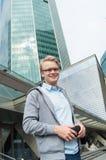 Hombre joven casual sonriente con el pelo rubio cerca del centro de negocios Fotos de archivo