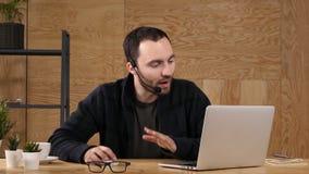 Hombre joven casual sonriente con las auriculares usando el ordenador en una oficina brillante metrajes
