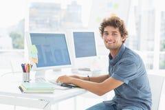 Hombre joven casual sonriente que usa el ordenador en oficina Fotografía de archivo libre de regalías