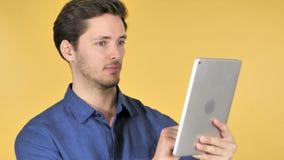 Hombre joven casual usando la tableta en fondo amarillo metrajes
