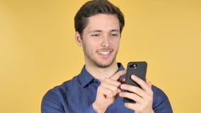 Hombre joven casual usando Smartphone en fondo amarillo almacen de video