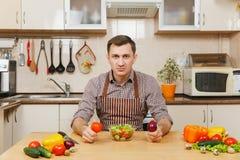 Hombre joven caucásico hermoso, sentándose en la tabla Forma de vida sana El cocinar en el país Prepare el alimento imagenes de archivo