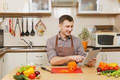 Hombre joven caucásico hermoso, sentándose en la tabla Forma de vida sana El cocinar en el país Prepare el alimento fotos de archivo libres de regalías