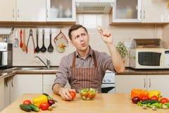 Hombre joven caucásico hermoso, sentándose en la tabla Forma de vida sana El cocinar en el país Prepare el alimento imágenes de archivo libres de regalías