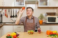Hombre joven caucásico hermoso, sentándose en la tabla Forma de vida sana El cocinar en el país Prepare el alimento foto de archivo
