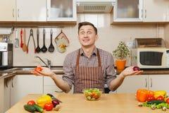 Hombre joven caucásico hermoso, sentándose en la tabla Forma de vida sana El cocinar en el país Prepare el alimento fotos de archivo
