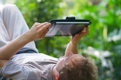 Hombre joven caucásico que descansa sobre la hierba verde y Imágenes de archivo libres de regalías