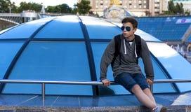 Hombre joven cerca de una bóveda de cristal en una calle de la ciudad Imagenes de archivo