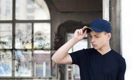 Hombre joven cerca de una ventana rota vieja Fotografía de archivo