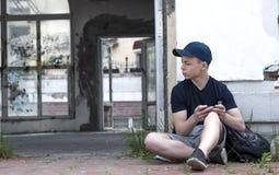 Hombre joven cerca de una ventana rota vieja Imagen de archivo libre de regalías