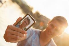 Hombre joven cerca del río que toma Selfie Fotos de archivo libres de regalías