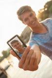 Hombre joven cerca del río que toma Selfie Imagen de archivo libre de regalías