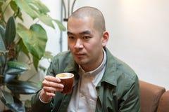 Hombre joven chino con el pendiente en café con el casquillo Imagen de archivo