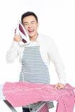 Hombre joven chino que plancha su ropa Fotografía de archivo libre de regalías
