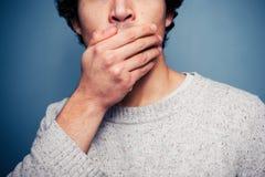 Hombre joven chocado con su mano en su boca Imagen de archivo